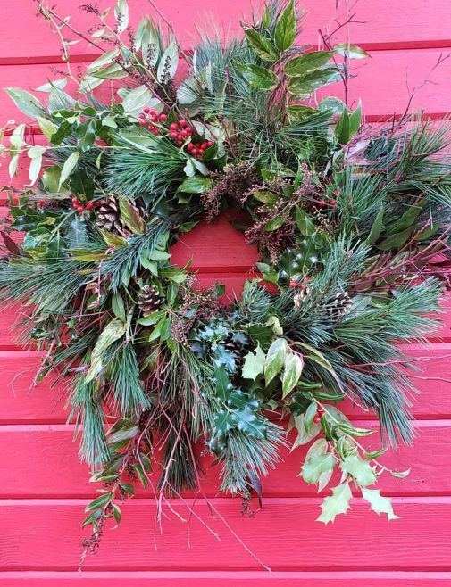Natural holiday wreath on red wall
